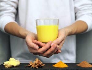 Hands holding a glass of golden milk (turmeric milk) - alternative medicine concept, naturopathy