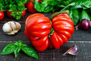 A large ripe red tomato with basil on a wooden table. Italian tomato variety.