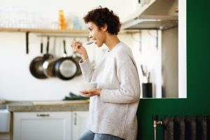 Profile of happy young woman eating cereal at home kitchen