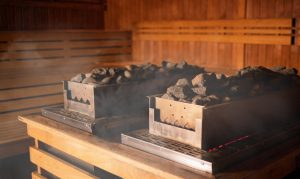 Heater in sauna with hot stones among steam