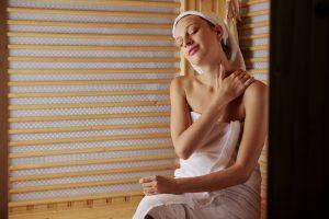 Woman enjoying self massage in sauna